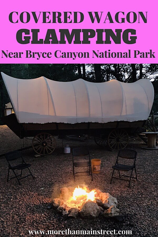 Bryce Canyon Glamping experience featured by top US family travel blog, More Than Main Street: image of   Glamping in a covered wagon at night by the fire in Utah.