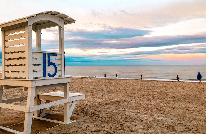 Top 10 fun things to do in Carolina Beach NC featured by top US travel blog, More than Main Street: beach and lifeguard stand.
