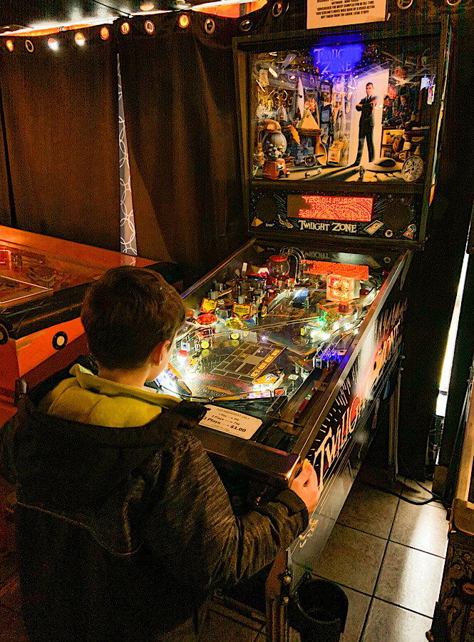 Boy playing a pinball machine in the Pinball Museum in Asheville NC.
