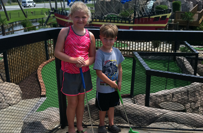 A little girl and a little boy playing miniature golf in the Outer Banks of North Carolina..