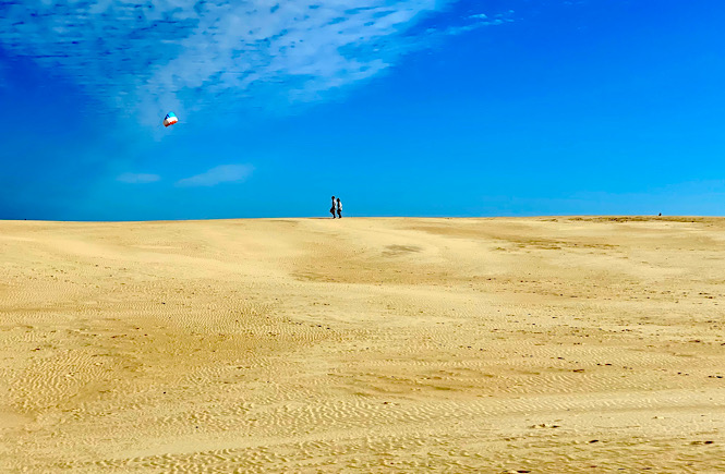 Jockey's Ridge State Park sand dunes! Image is someone flying a kite in the distance on empty sand dunes.