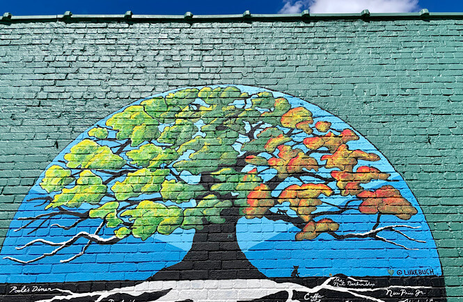 Raleigh city of oaks mural next to the All are Welcome mural in downtown Raleigh.