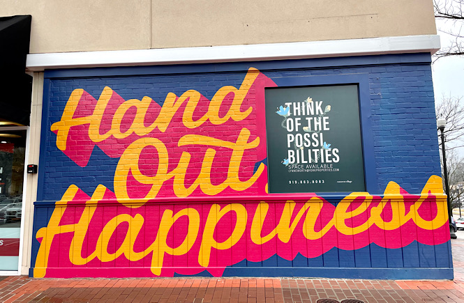 Hand out happiness mural at Cameron Village in Raleigh NC- beautiful mural in orange and pink with a blue background!