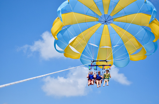 Parasailing in the Outer Banks is the perfect road trip adventure for all ages- blue skies with a blue and yellow parasailing with three happy people in the air!