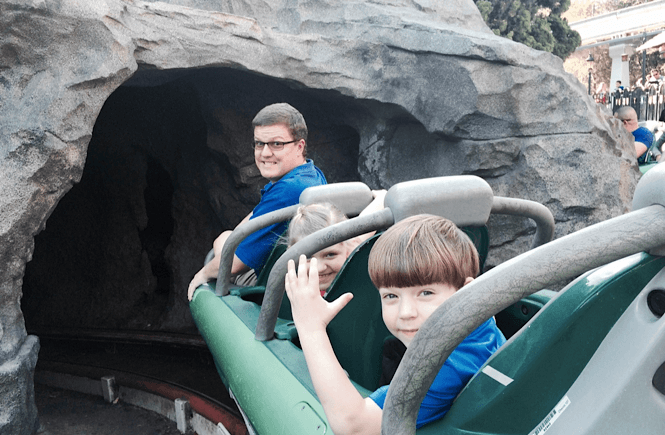 One of the most fun day trips from San Diego with kids is of course Disneyland!! Image of a Dad and two kids on a ride at Disneyland.