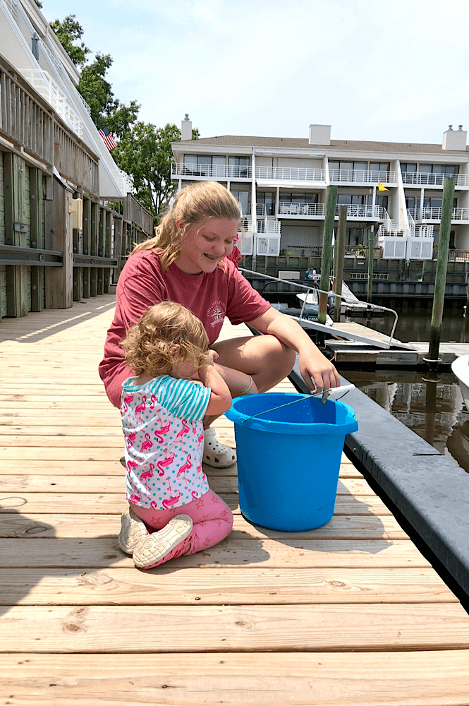 A toddler and a teenager looking at some fish in a bucket at a marina.
