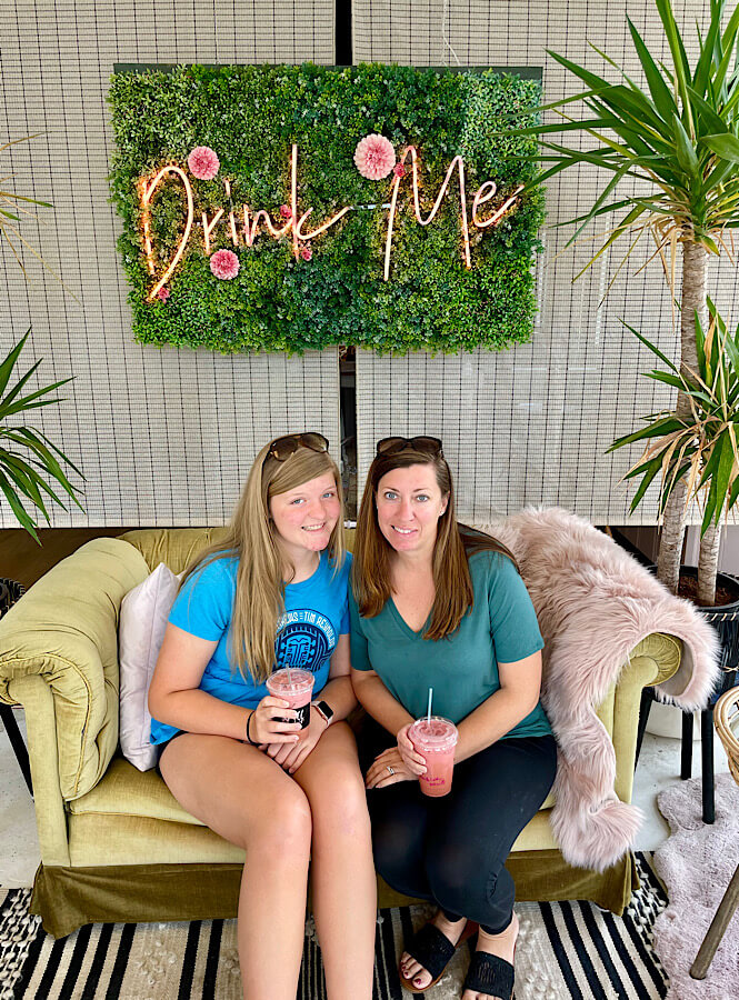"""The super insta-worthy spot at Spill coffee shop has a couch with a sign over it that says """"Drink Me""""."""