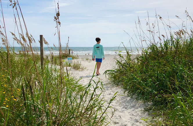 A boy walking to the Wrightsville Beach Mailbox.