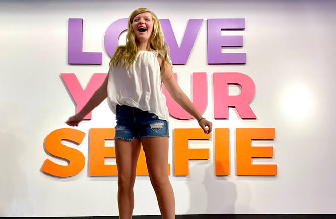 """""""Love your selfie"""" sign with a teenager girl jumping for joy!"""
